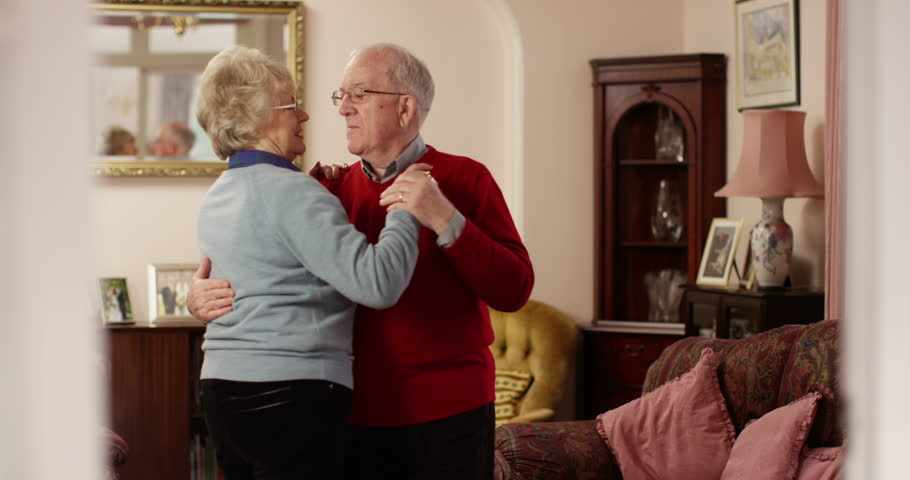 Happy senior couple dancing at home. Shot in slow motion