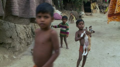 Baruipur, India - CIRCA 2013 - Child holding puppy as other village kids are nearby
