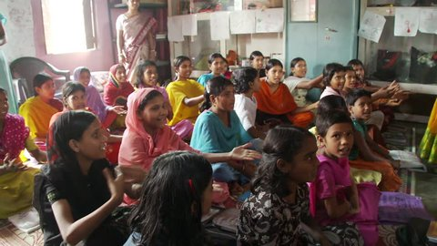 Baruipur, India - CIRCA 2013 - Girls in school sitting on mats and singing and using hand gestures