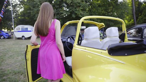 Attractive woman sit inside yellow retro car 4K. Brown hair woman in purple short dress sit in to old retro beetle car and looks back. Old car cabriolet.