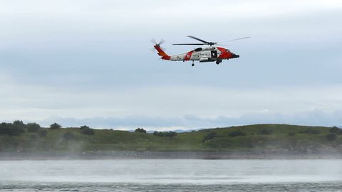 Coast Guard helicopter hovers over water for training maneuvers, flies away, slowly, near coastline off Kodiak Island, Alaska.1080p