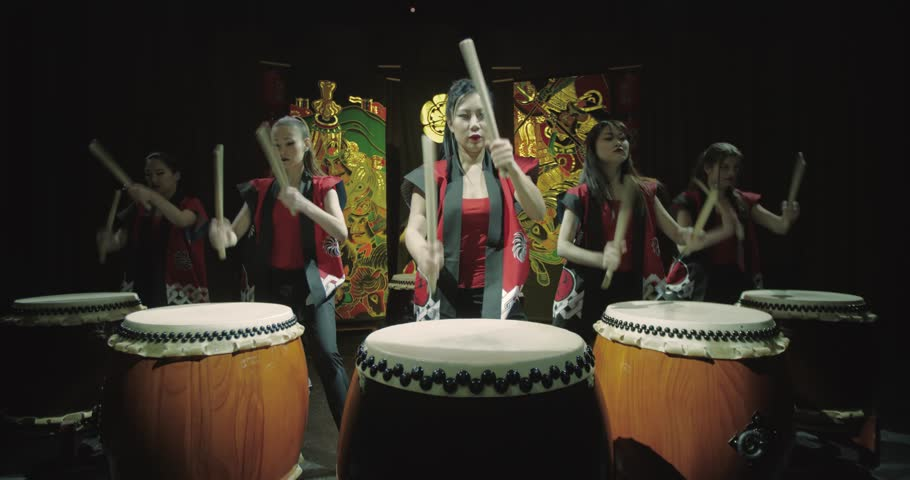 a group of Japanese Taiko drummers girls performs on stage,a dark background