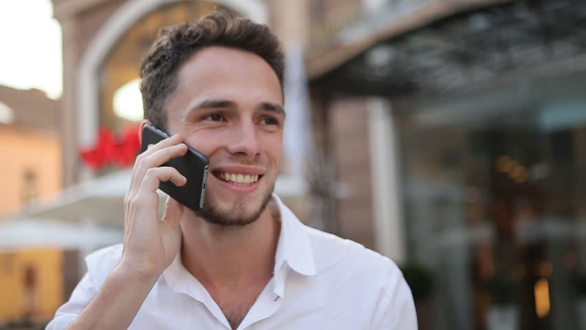 Young male holding on the phone, smiling and touching his neck. | Shutterstock HD Video #14238110