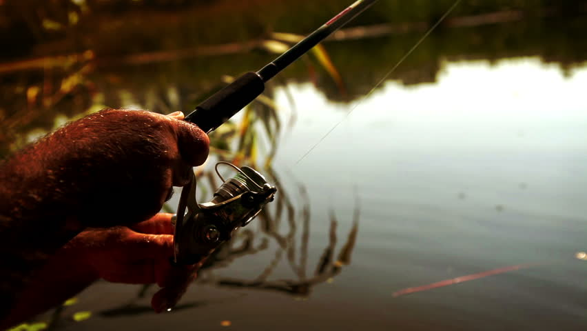 Slow-motion footage of a spinning rod in the hands of a amateur fisherman | Shutterstock HD Video #14244440