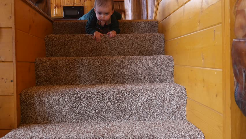 A dolly shot of a baby boy going precariously up or down the stairs in his home