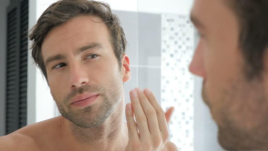 Handsome man in bathroom shaving with electric razor
