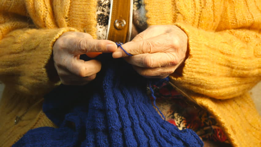 Grandmother knits a scarf
