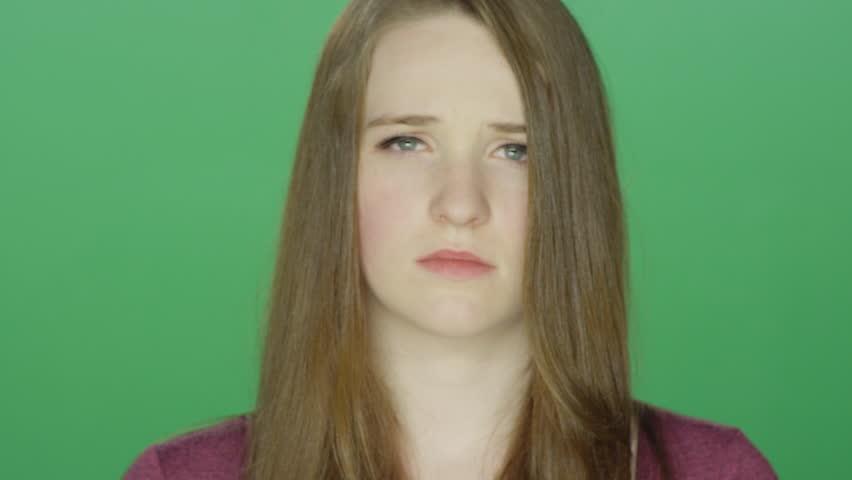 Cute redhead looking sad, on a green screen studio background #14360560
