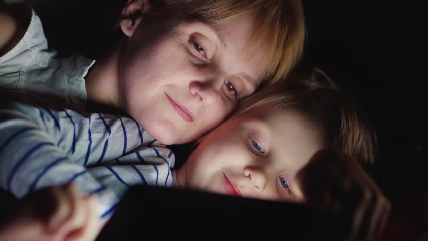 Mum with a blonde girl enjoying tablet. Lying side by side face to face, the light from the tablet screen illuminates their faces   Shutterstock HD Video #14395870
