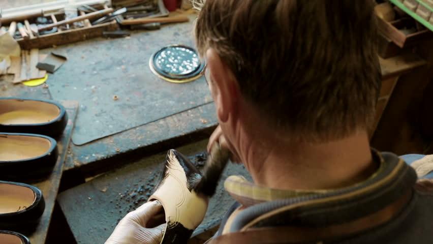 Clog maker is painting a clog black