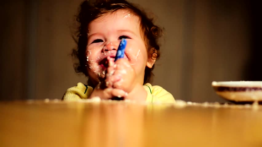little cute baby in the kitchen smeared face and laughs