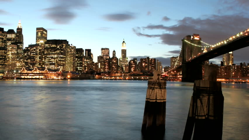 Slow pan of a time-lapsed shot of clouds in shades of pink and purple passing over the New York City skyline as darkness falls. | Shutterstock HD Video #1444960