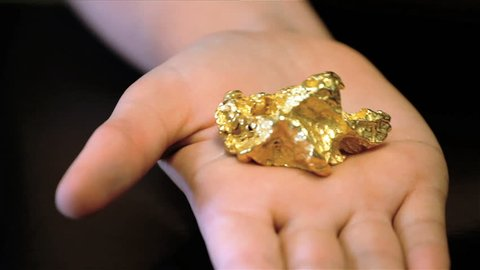 Gold Nugget. A real gold nugget being displayed on a woman's hand to give a sense of scale.