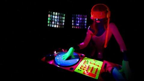 sexy female DJ mixes in a club in UV fluorescent costume