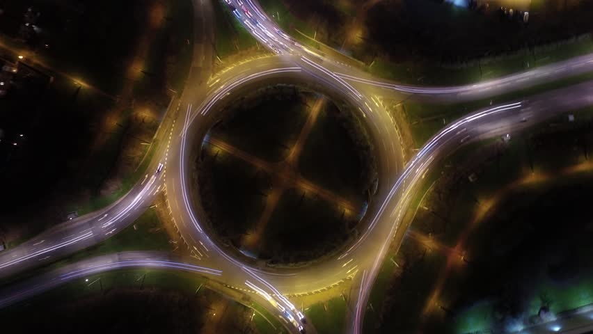 Aerial time lapse shot directly above a roundabout in the UK at night, with the camera locked straight down. This clip loops seamlessly. Ungraded version.