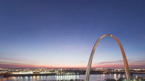 4K Time lapse tilt shot aerial view St Louis Gateway Arch at sunrise with boat traffic on the river and red colored clouds