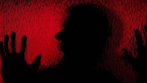 The silhouette of a zombie moving behind a frosted red glass. Horror Halloween themed shot.