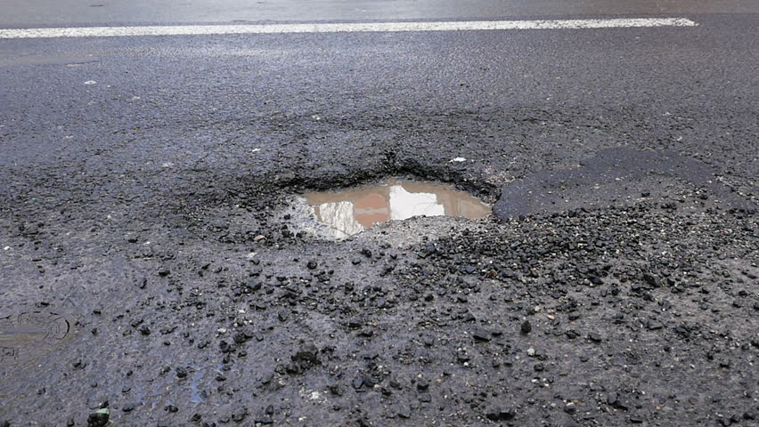 Cracked asphalt, pothole on the street - bus is passing by, slow motion