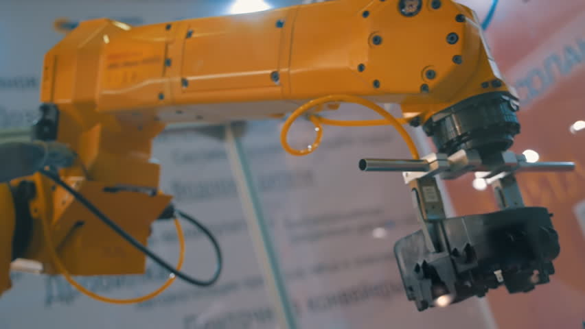 Industrial robot manipulator yellow color performs movements that are programmed in the control unit. Shot in motion
