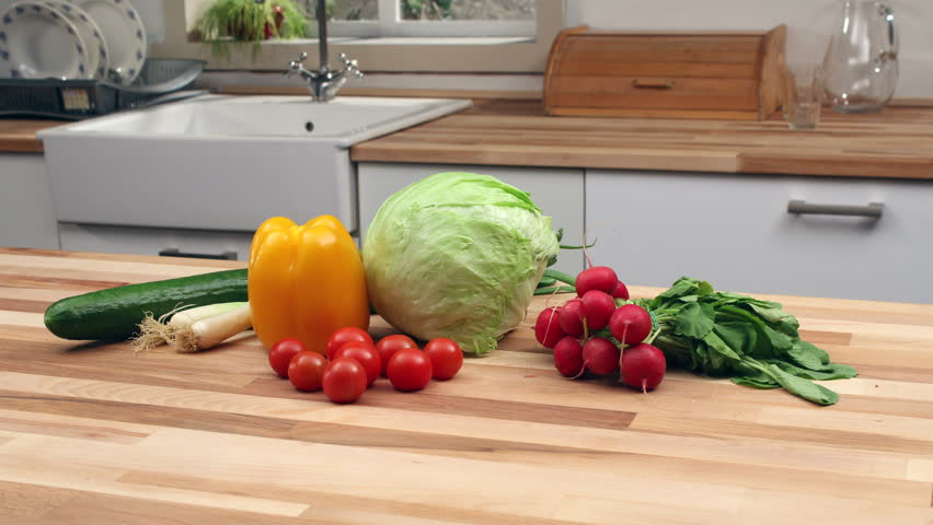 Kitchen Counter With Food cooking preparation. moving vegetables on wooden kitchen