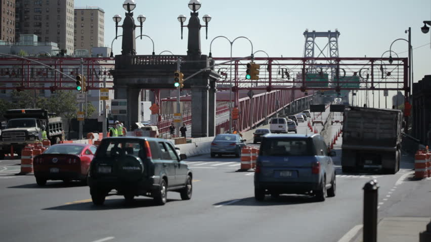 traffic moving onto the Williamsburg bridge from the Manhattan side with focus on the distant bridge and shallow depth of field to obscure license plates etc.