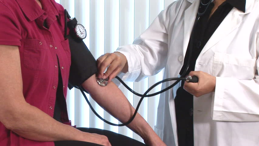young doctor giving a blood pressure exam to a patient
