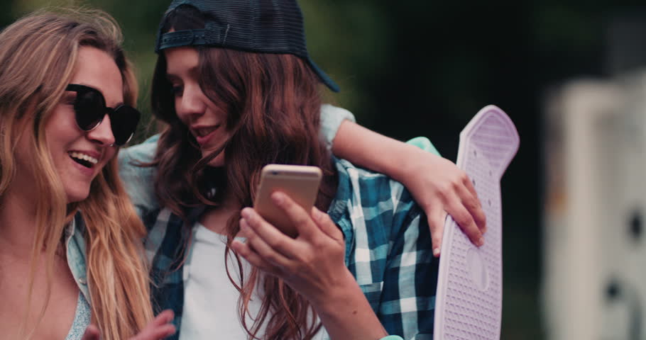 Two teenaged girl friends wearing hipster style clothing smiling at something amusing on a smart phone while standing outside