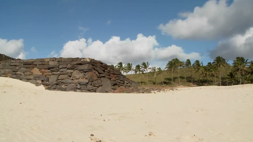 A pan across to Easter Island statues on a beach in the distance.