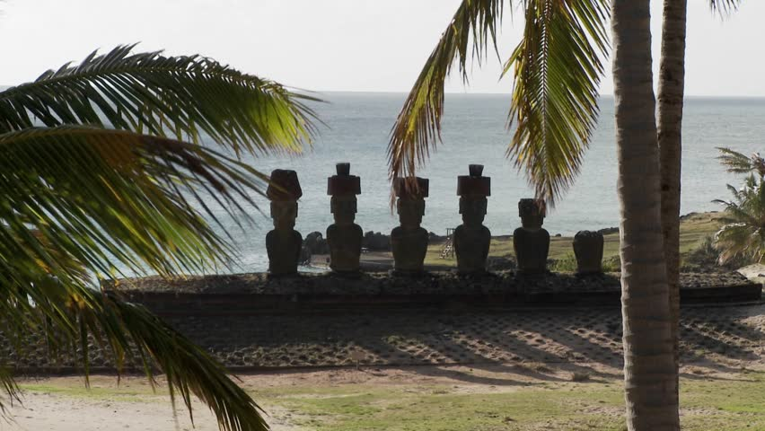 Easter Island statues with the ocean in the background and palms waving.