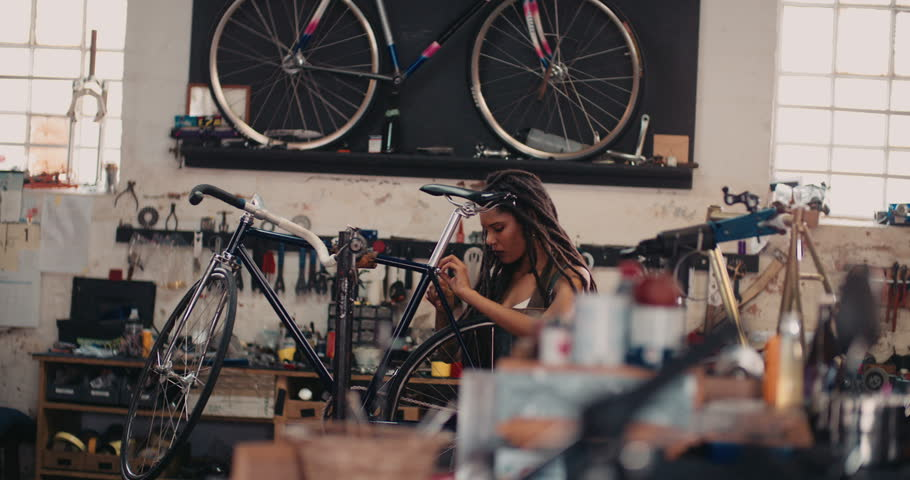 Afro-american craftswoman repairing a bicycle in her bike repair workshop with tools and spares around her