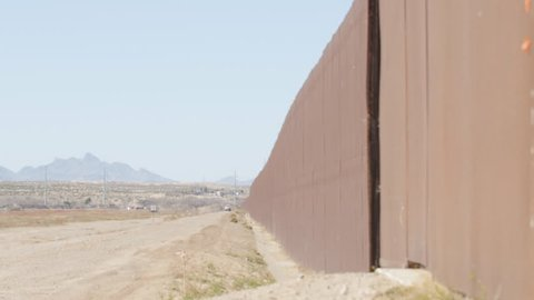A pan shot looking at the length of the fence on the US and Mexico border on a sunny afternoon.