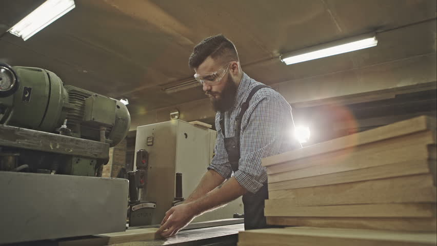 Industrial carpenter worker operating wood folding machine during wooden door furniture manufacturing. RAW video record.