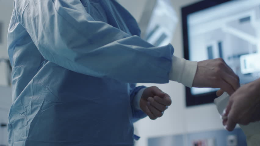 Nurse Helping to Surgeon to Put Protective Gloves on Before Operation. Shot on RED Cinema Camera.