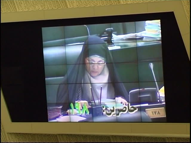 Tehran, Iran - 2005 - Shot of a video screen in the Iranian Parliament showing MP Mrs Rafat Bayat (2005) sitting in a chair with a microphone in front of her.