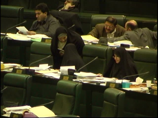 Parliament, Tehran, Iran - 2005 - Iranian male and female MPs are segregated, sitting in separate rows in the Iranian Parliament. MP Mrs. Rafat Bayat is talking to her colleague.