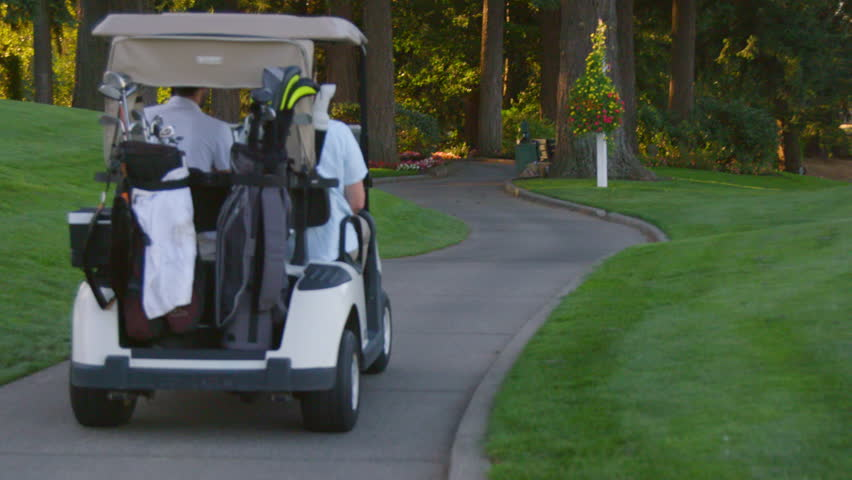 Two golfers ride in a golf cart on a beautiful golf course