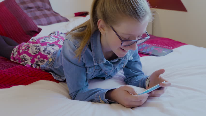 Young girl with long brown hair and wearing glasses lying on bed watching a video on her smartphone laughing and smiling. Filmed on a mid shot in 4K. | Shutterstock HD Video #14826220