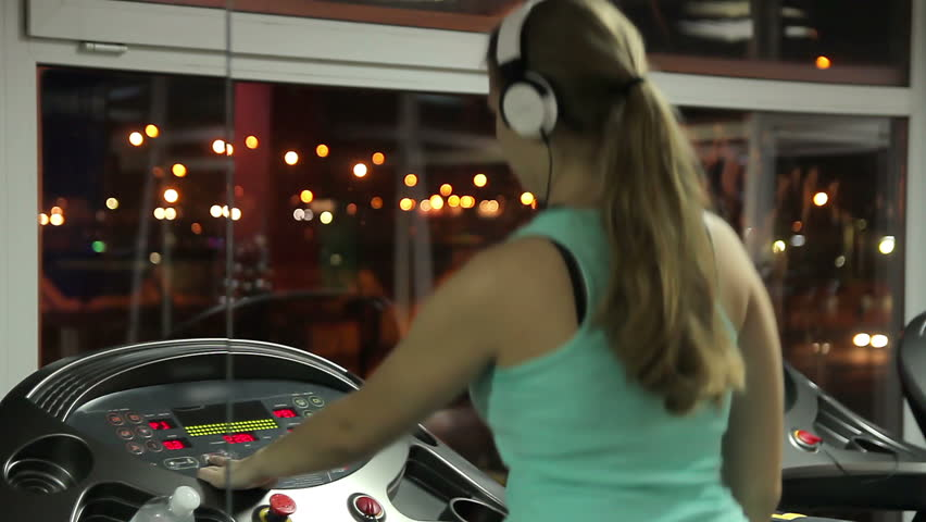Young female wearing earphones switches off treadmill, finishes workout in gym | Shutterstock HD Video #14826340