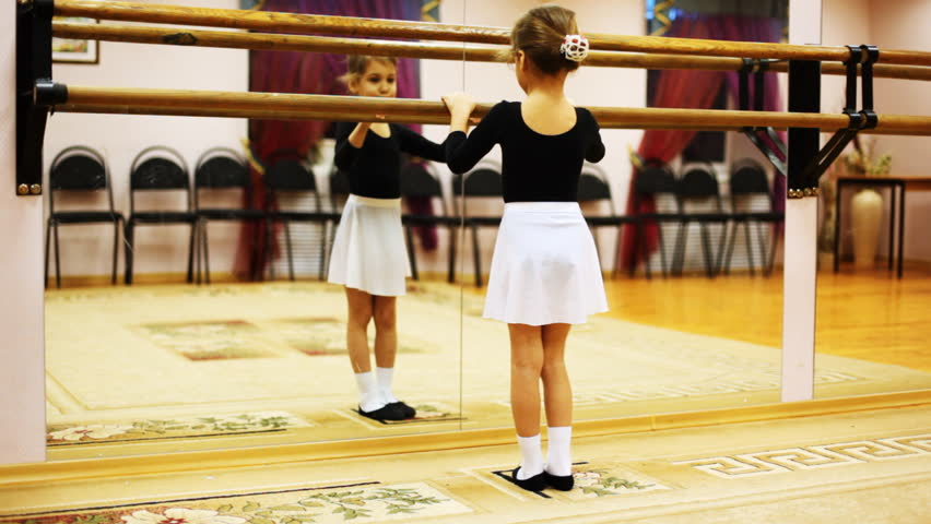 cute little girl does ballet leg movements while facing mirror in dance hall