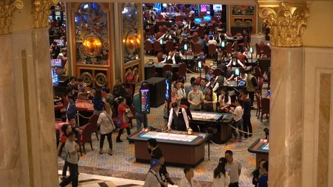 MACAU - 24 OCTOBER 2015: Crowds of mainland Chinese visitors are gambling inside a large casino in Macau