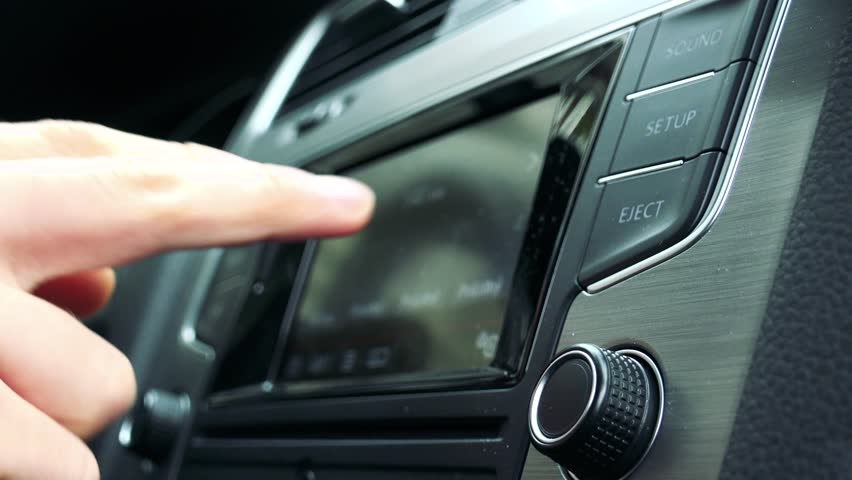 young man uses radio in the modern car - touch screen