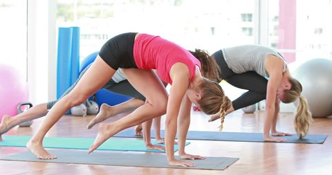 Smiling women stretching their bodies on an exercise mat