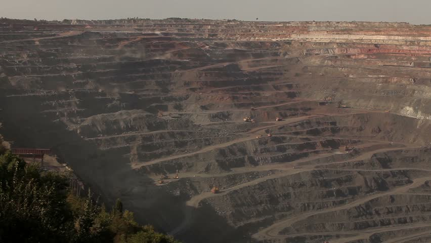 the iron ore opencast mining quarry, Large, open-pit iron ore mine showing the various layers of soil and iron rich ore,  industrial exterior, ore mining quarry, sunny day, summer, mining of iron