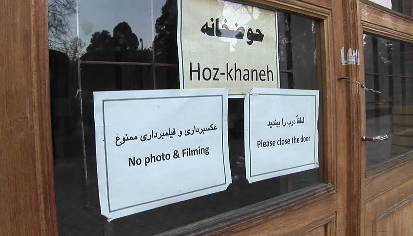 Signs on a window in Iran. Prohibits photography and ask visitors to close the door.