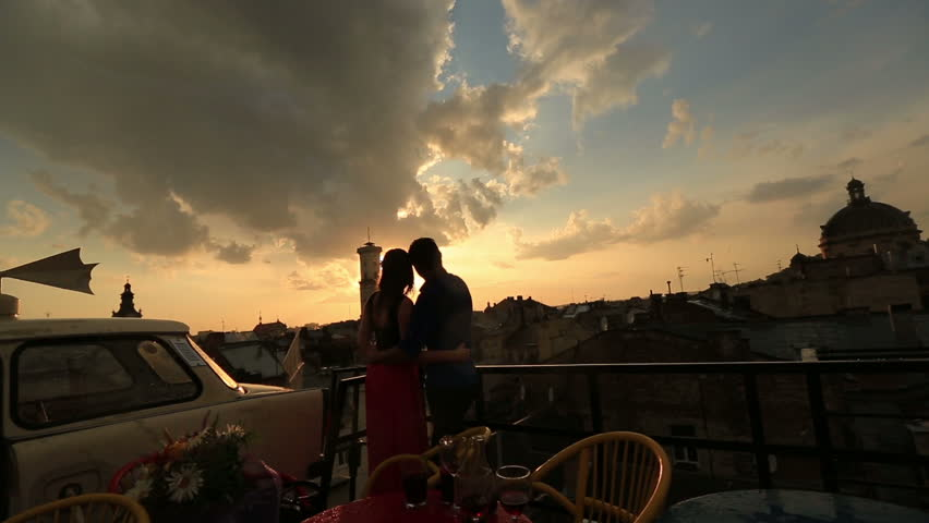 Silhouette of young loving couple softly hugging and enjoying the view on the rooftop of ancient city building close up. Amazing sunset with old tower on the background | Shutterstock HD Video #14994910