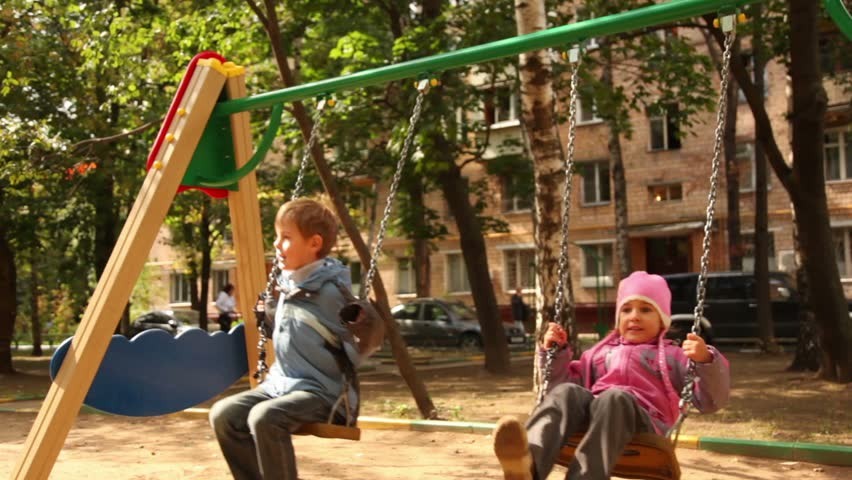 Boy and little girl sway on swing at playground