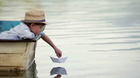 Boy wearing wicker hat sitting in the boat setting his paper boat on a journey