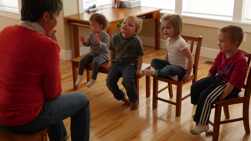 Team of successful creative designers approach the camera stock a woman teaching preschool to toddlers in her home while they sit on chairs 4k ccuart Gallery
