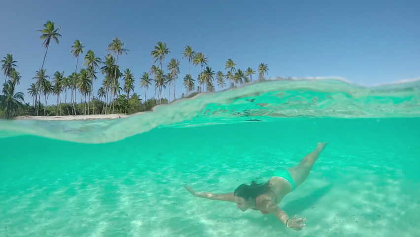 SLOW MOTION HALF UNDERWATER CLOSE UP: Young woman in colorful bikini swimming under water surface in amazing crystal clear blue lagoon in front of beautiful tropical island on perfect summer day