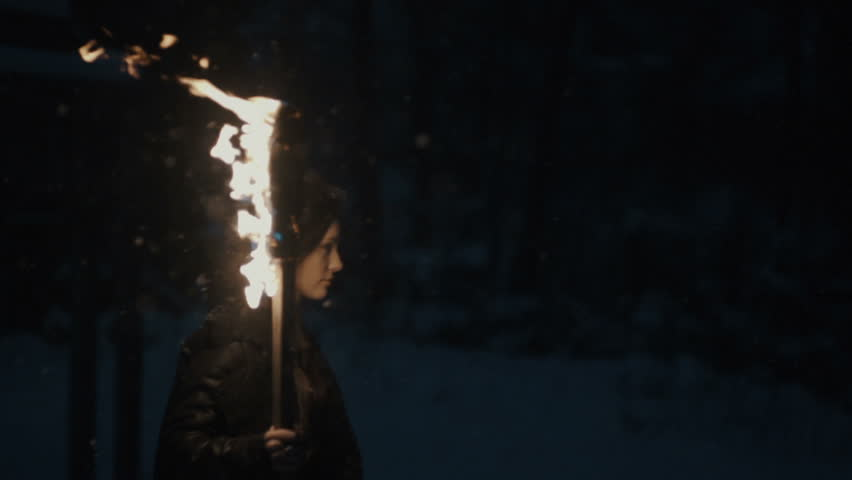 Portrait of a young mystic woman walking in the dark forest with a torch. Young woman with torch over dark night background. Slow motion. Winter season.